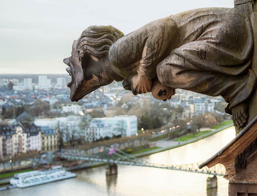 Kontraste: Ein mittelalterlicher Gargoyle scheint über die frankfurter Skyline zu rufen